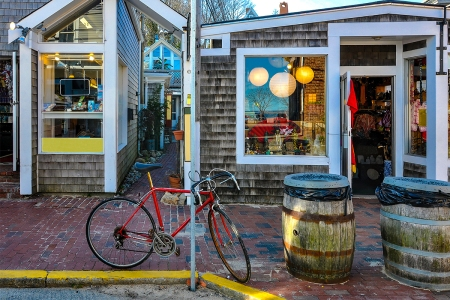 A red bicycle sitting in front of shops in Cape Cod