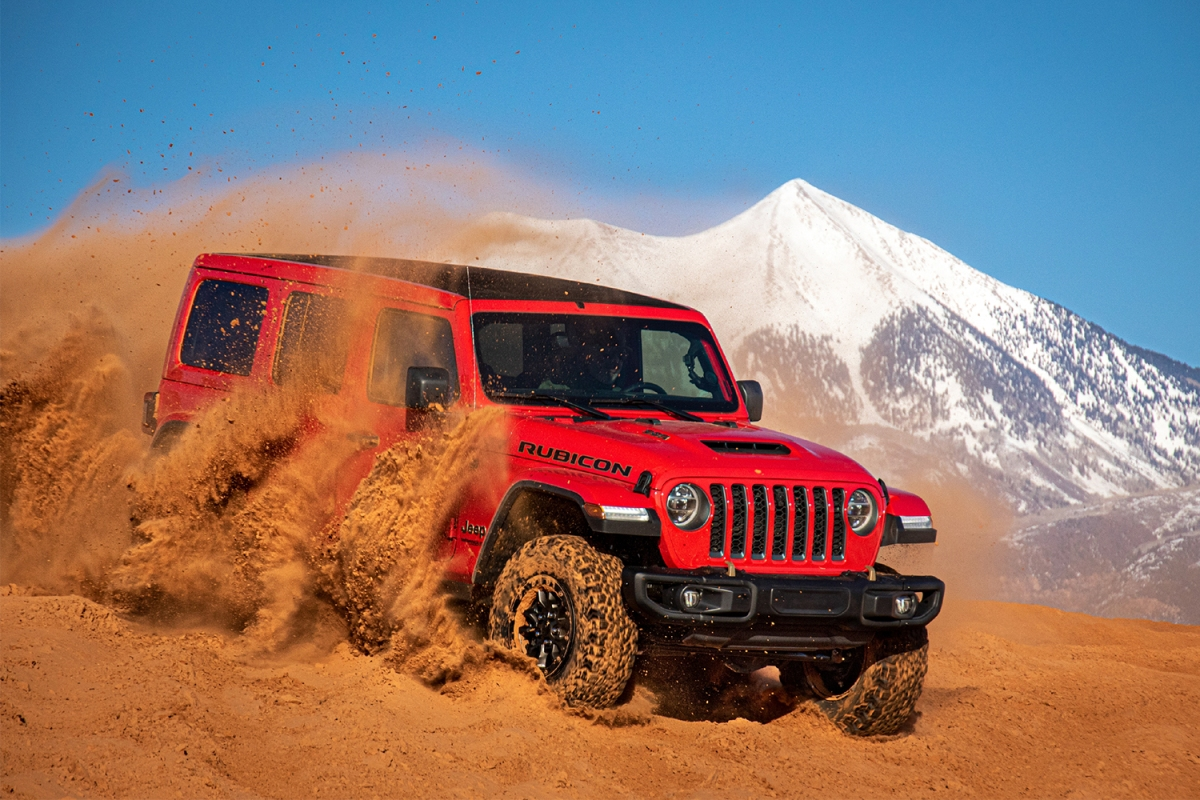A red Jeep Wrangler Rubicon 392, the first-ever Wrangler with a V8 engine, churning up sand dunes in front of a snow-capped mountain