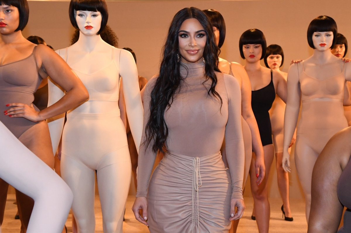 Kim Kardashian celebrates the launch of SKIMS at Nordstrom NYC. The star poses in a nude dress alongside mannequins outfitted in the brand's shapewear.