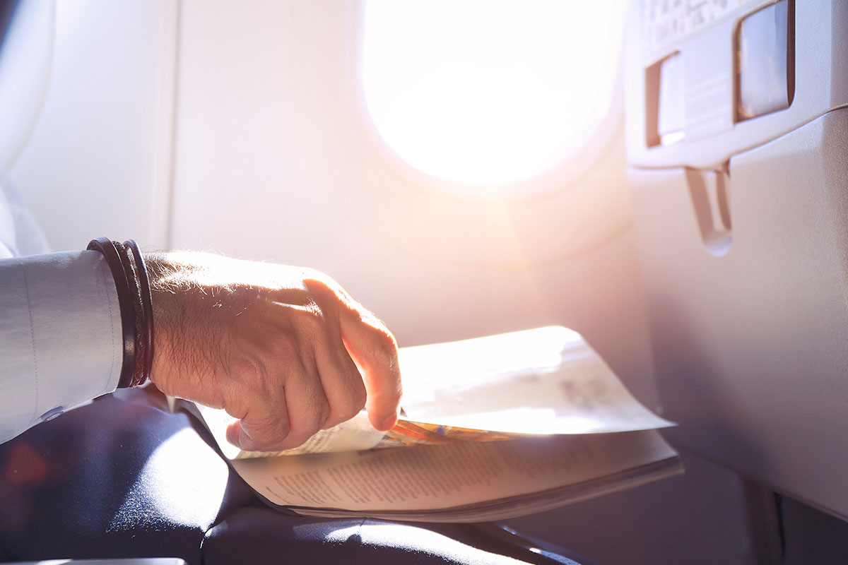 Man reading magazine in airplane - Close up shot of hand