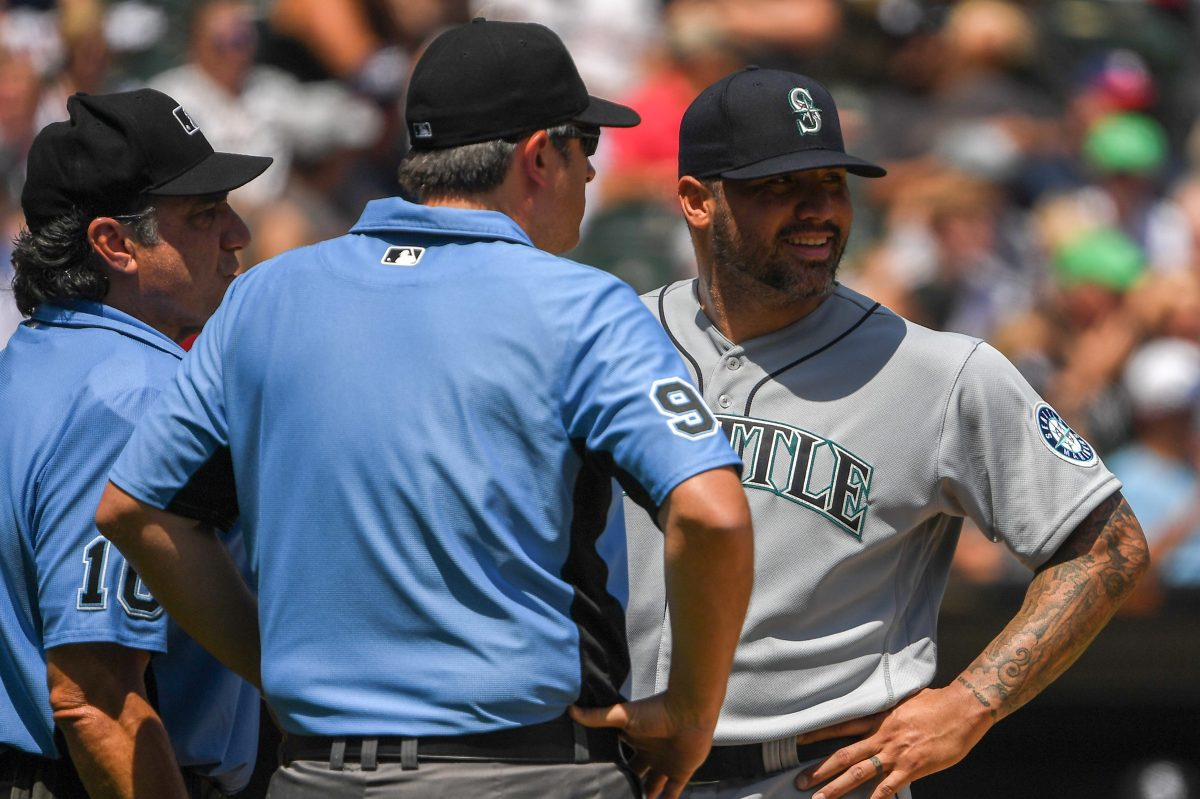 Umpires talk to Hector Santiago of the Seattle Mariners