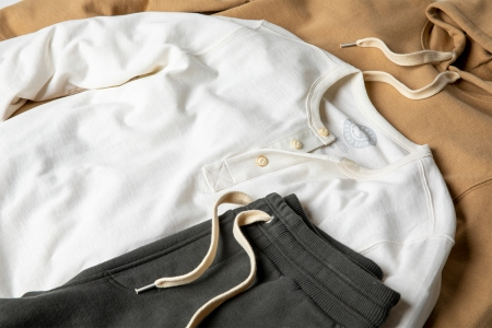 A white henley and grew sweatpants from Outerknown's Second Spin collection
