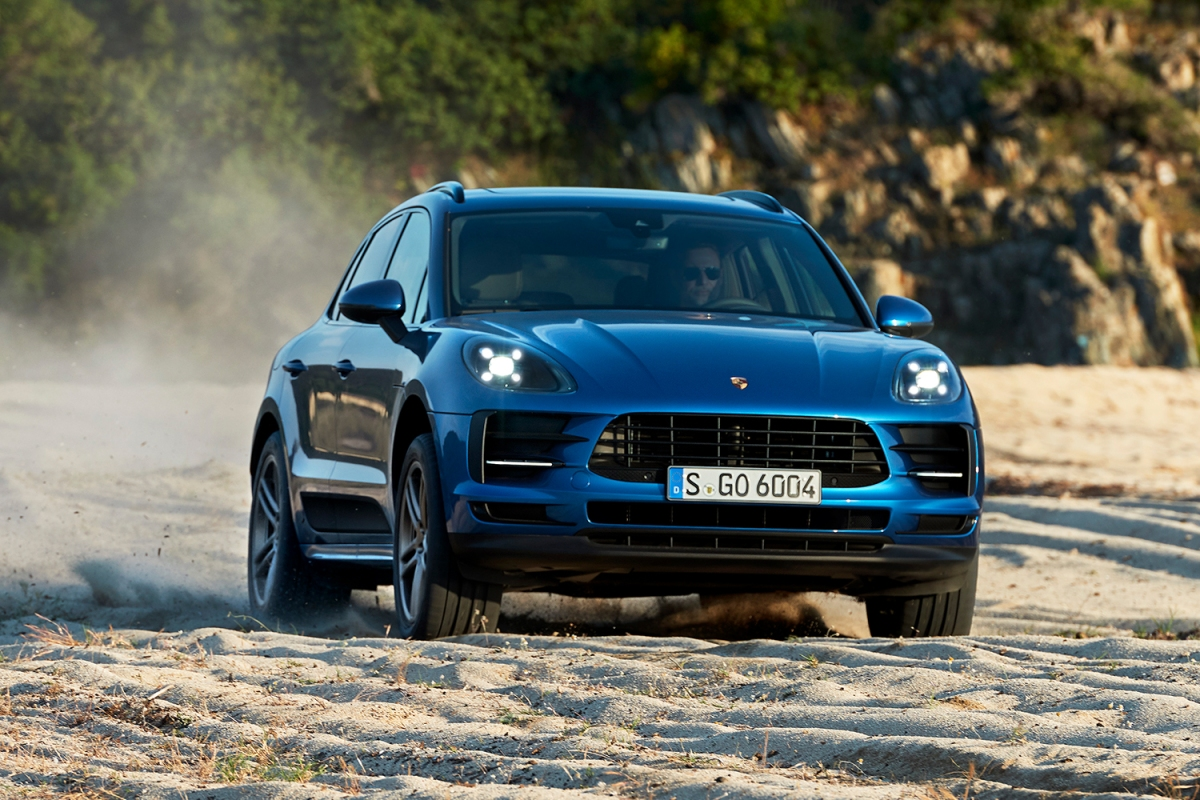 The new Porsche Macan SUV in blue driving on the sand