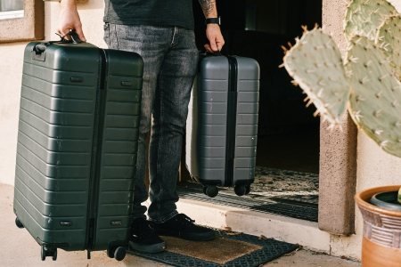 Man in jeans and black shirt stands near a door holding two rolling suitcases