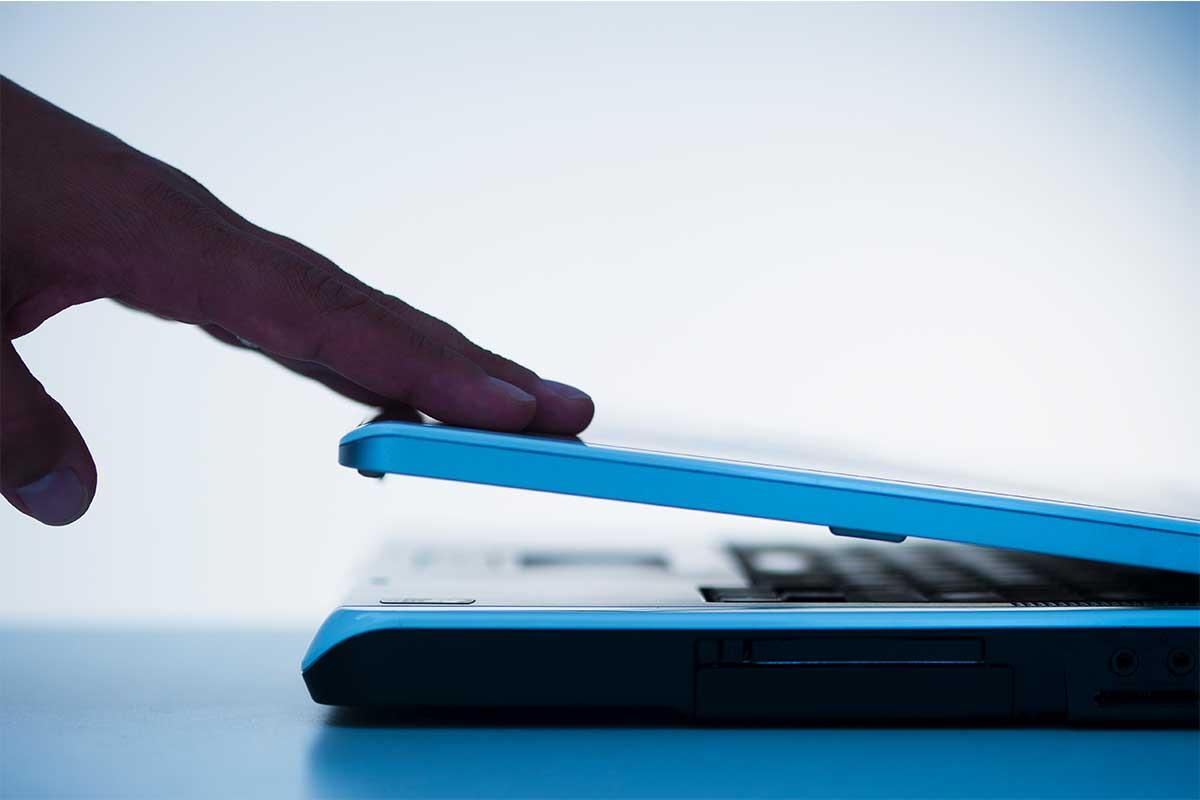 A hand closing a laptop computer