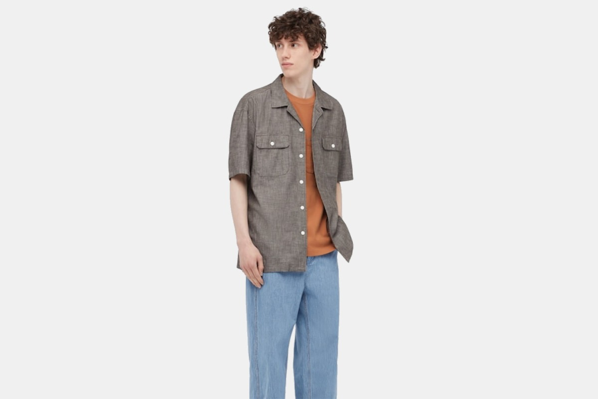 A model wearing the Chambray Short-Sleeve Workshirt from J.W. Anderson and Uniqlo