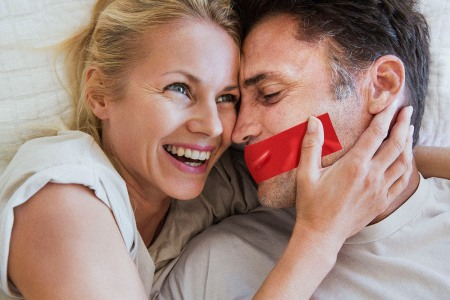 Couple in romantic embrace, woman laughing, man has tape over his mouth