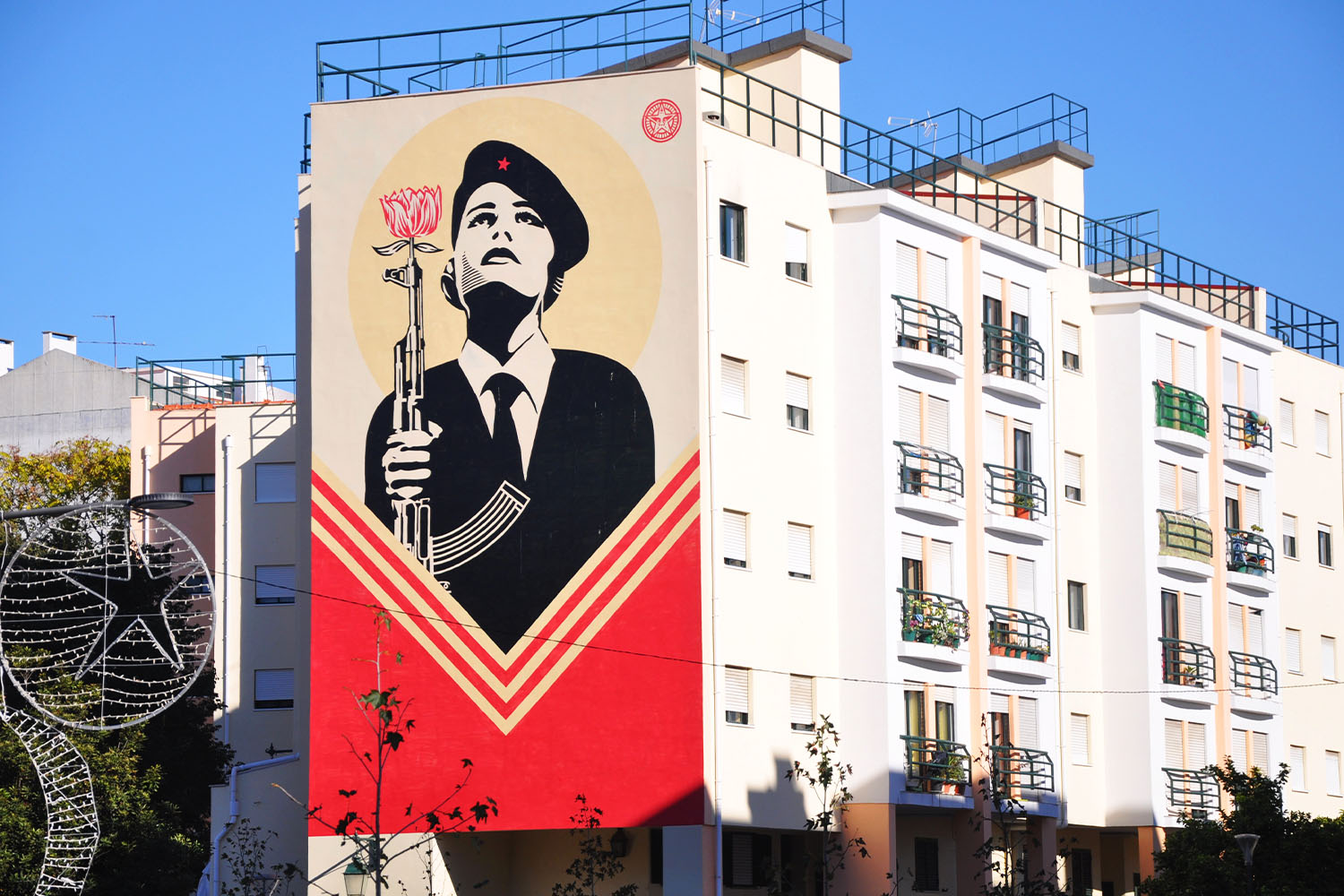 Shepard Fairey's mural of a woman wearing a revolutionary beret and holding a rifle with a carnation in the muzzle in Lisbon, Portugal