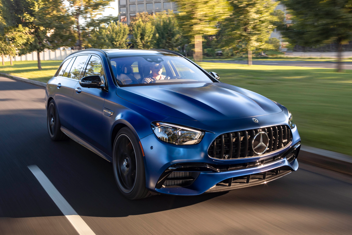 A blue 2021 Mercedes-AMG E63 S 4MATIC Wagon driving down the street. Want a high-performance station wagon? Read our review of this.