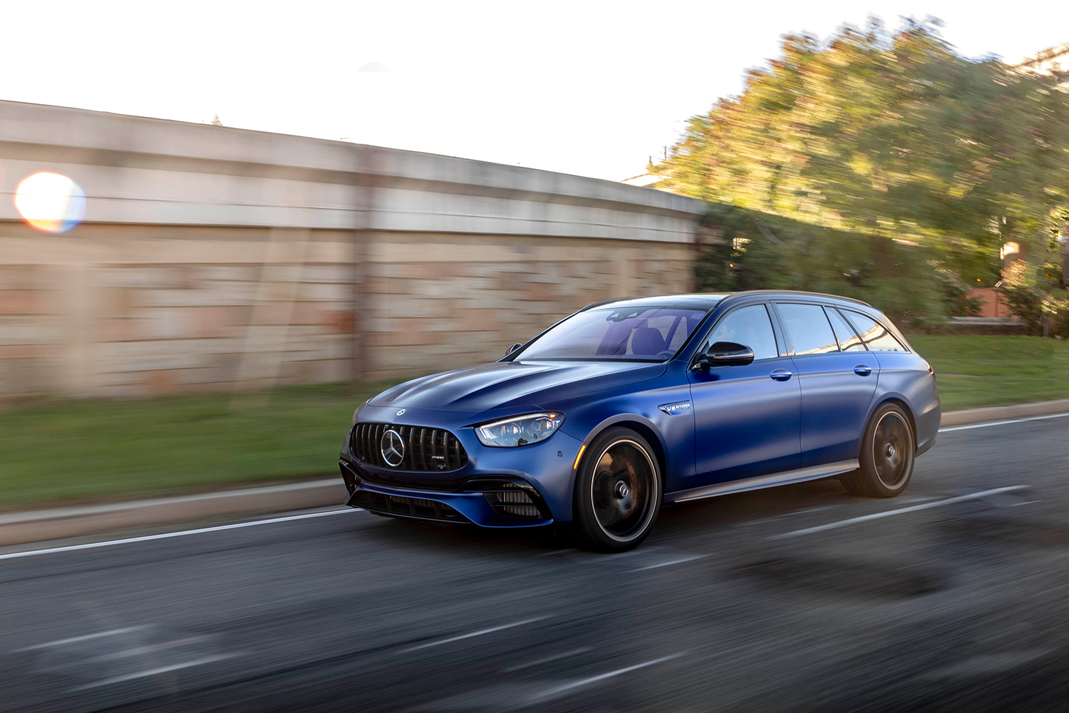 A blue 2021 Mercedes-AMG E63 S 4MATIC Wagon driving fast down city streets