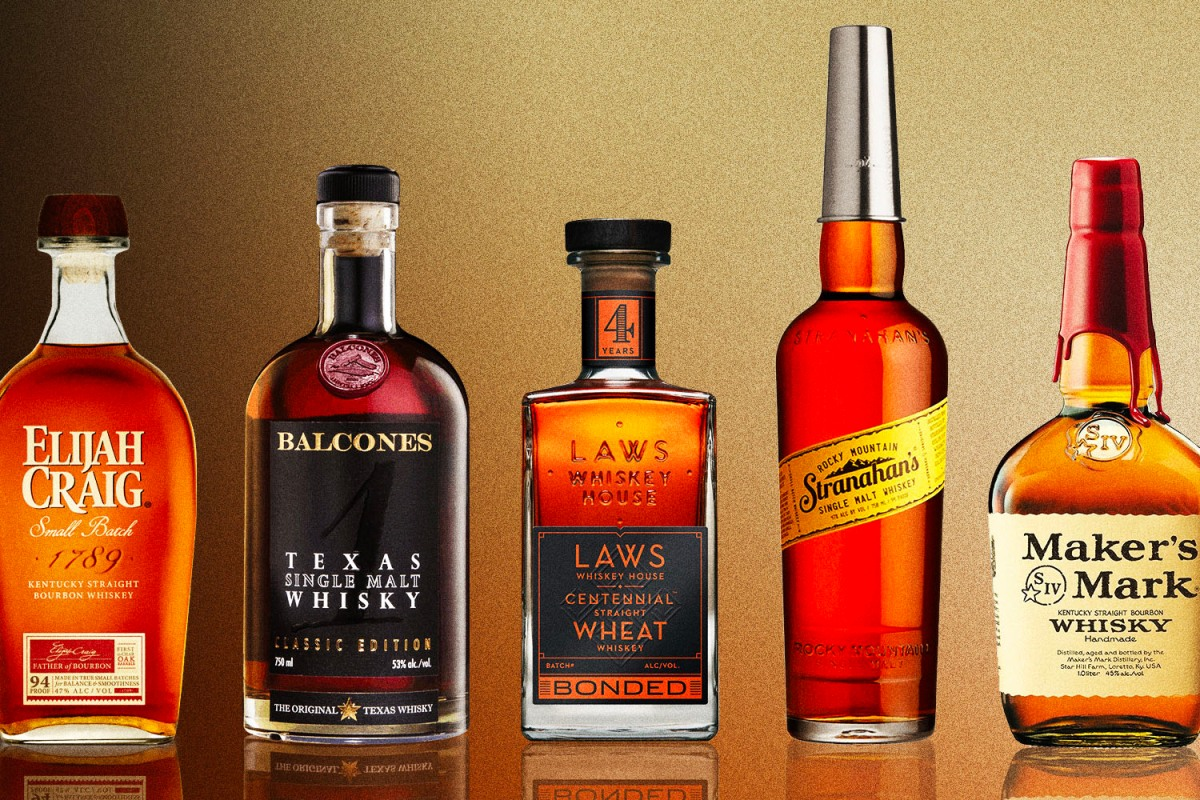 a line of whiskey bottles including elijah craig, balcones, laws, stranahan and makers mark