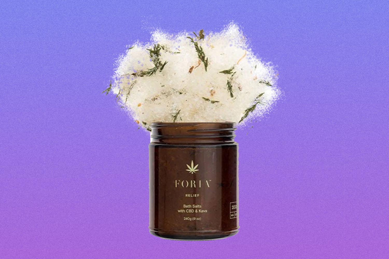Brown jar of Foria Intimacy Bath Salts on purple background
