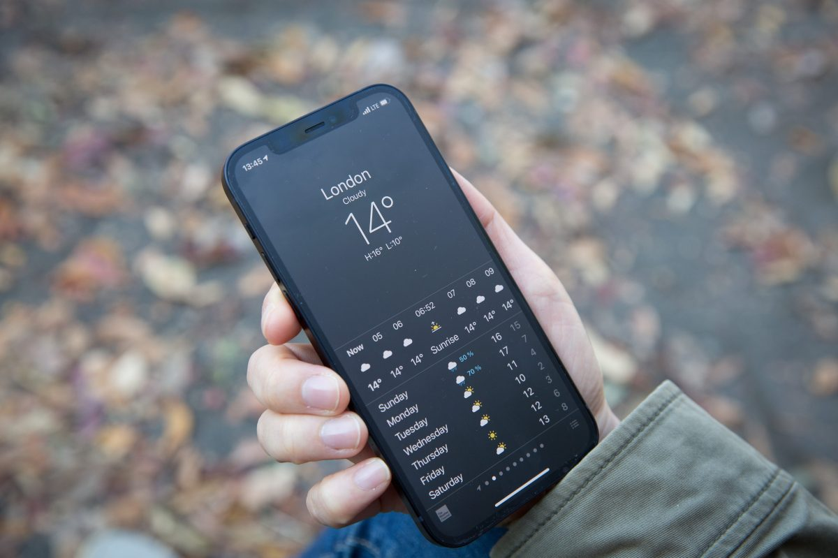 In this photo illustration a woman holds the new iPhone 12. The weather app for Apple reportedly won't show if it's 69 degrees.