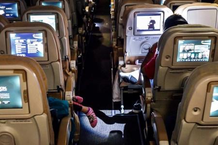 United Arab Emirates, Abu Dhabi International Airport, onboard cabin economy class Etihad Airways flight girl sleeping feet dangling.