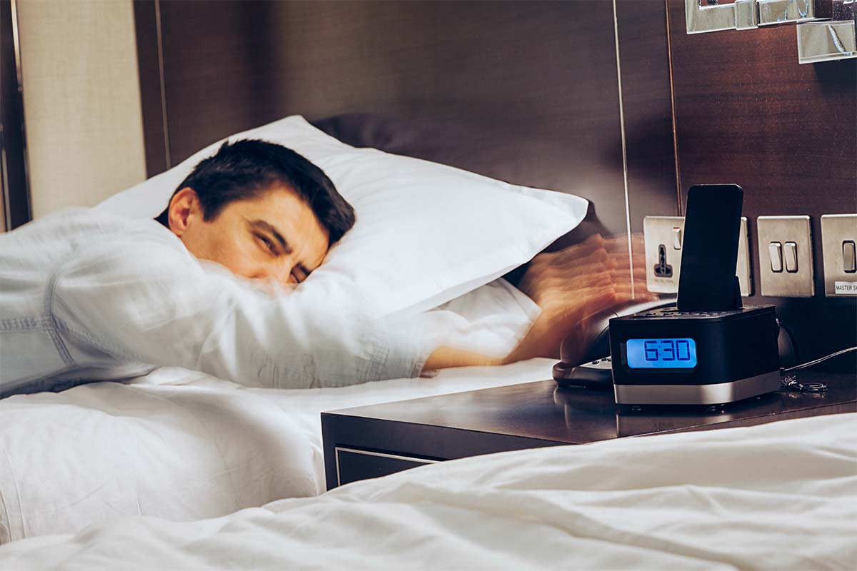 Businessman sleeping on bed and his hand reaching to turn off alarm clock with speedy action at 6:30 AM, Wake up early morning concept. Hotels with alarm clocks may soon become a thing of the past.