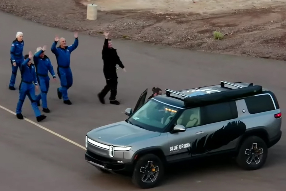Jeff Bezos, Mark Bezos, Wally Funk and Oliver Daemen waving at the site of the Blue Origin rocket launch next to a Rivian SUV electric adventure vehicle