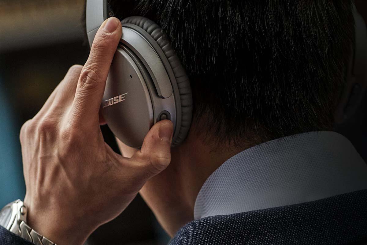 A man adjusting the controls on the Bose QuietComfort 35 II headphones