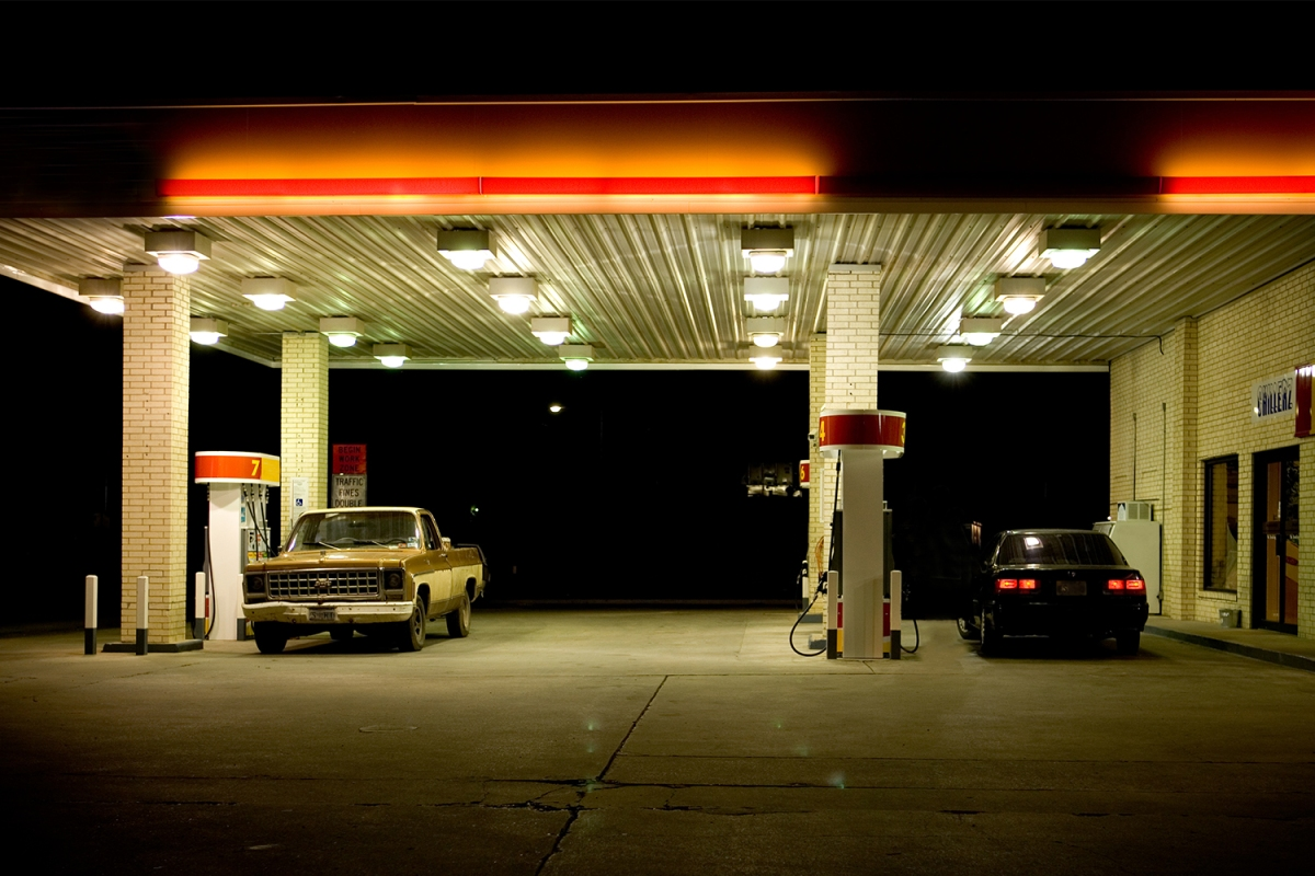 A pickup truck and black car at a gas station at night. Our love of gasoline is a problem when it comes to climate change.
