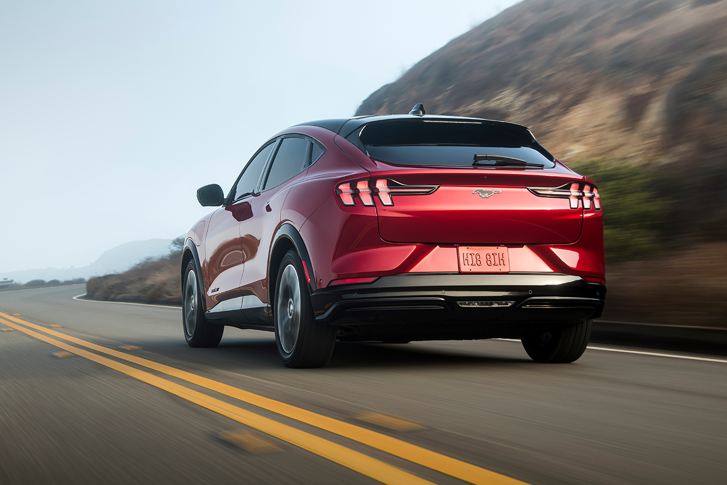 The rear end of a red Ford Mustang Mach-E driving down the road. Here's our review of the electric crossover.