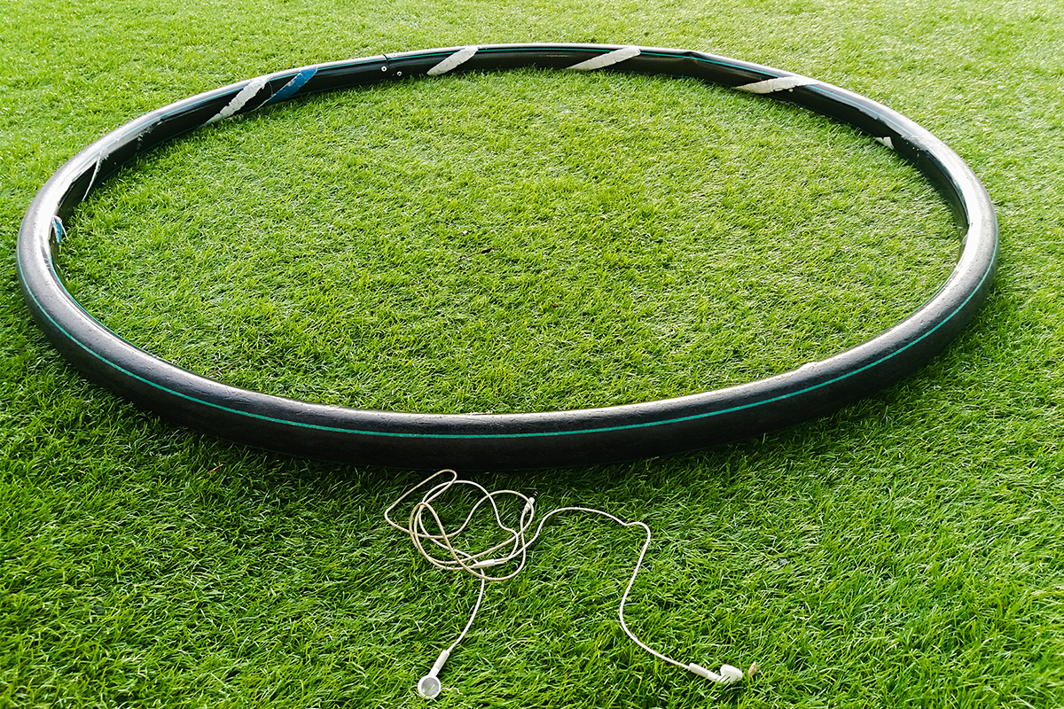 A weighted hula hoop, used for a trendy workout called hooping, sitting in the grass next to earbuds