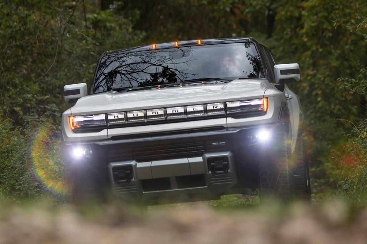 The GMC Hummer EV supertruck, a new electric pickup truck, driving through the dirt