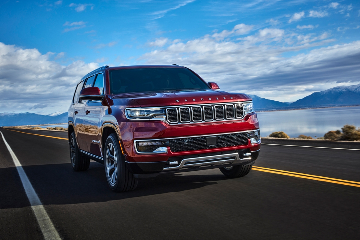 A red 2022 Jeep Grand Wagoneer driving along. The new luxury SUV has horrible gas mileage, proving we need stricter fuel economy standards.