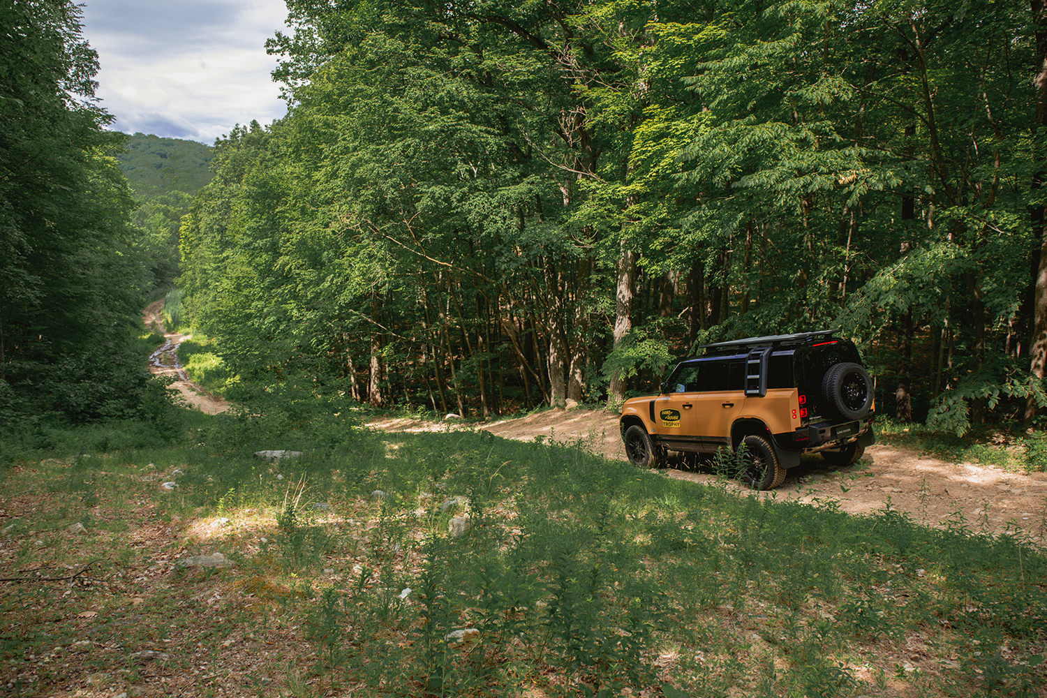 A Land Rover Defender Trophy Edition facing down an off-road trail, like one at the company's Biltmore Driving Center