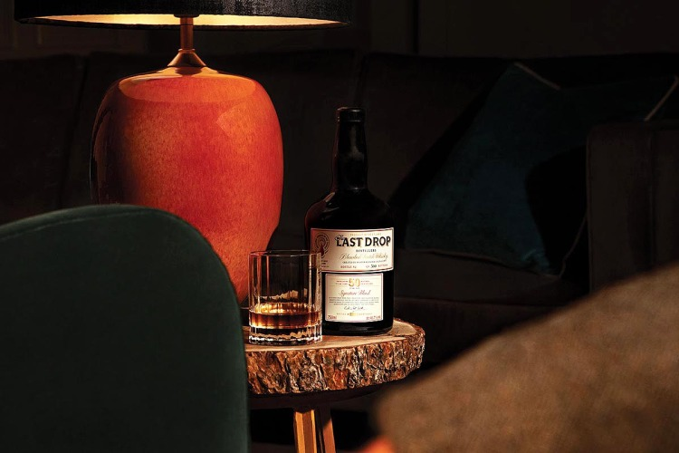 a bottle and a glass of 50 Year Old Signature Blended Scotch Whisky by The Last Drop Distillers, now available
