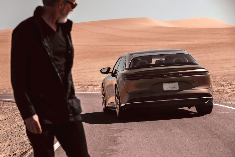 A man in the foreground looking back at the Lucid Air, an electric sedan from Lucid Motors, which recently launched on the stock market thanks to a SPAC merger.