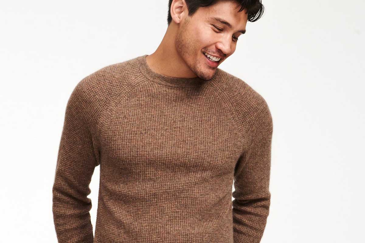 A man wearing a marled brown Cashmere Waffle Crewneck Sweater from Naadam, now 50% off