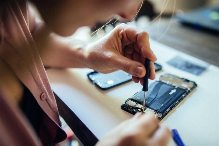 DIY repair mobile phone at home. Woman repairing mobile phone at home, changing damaged part.