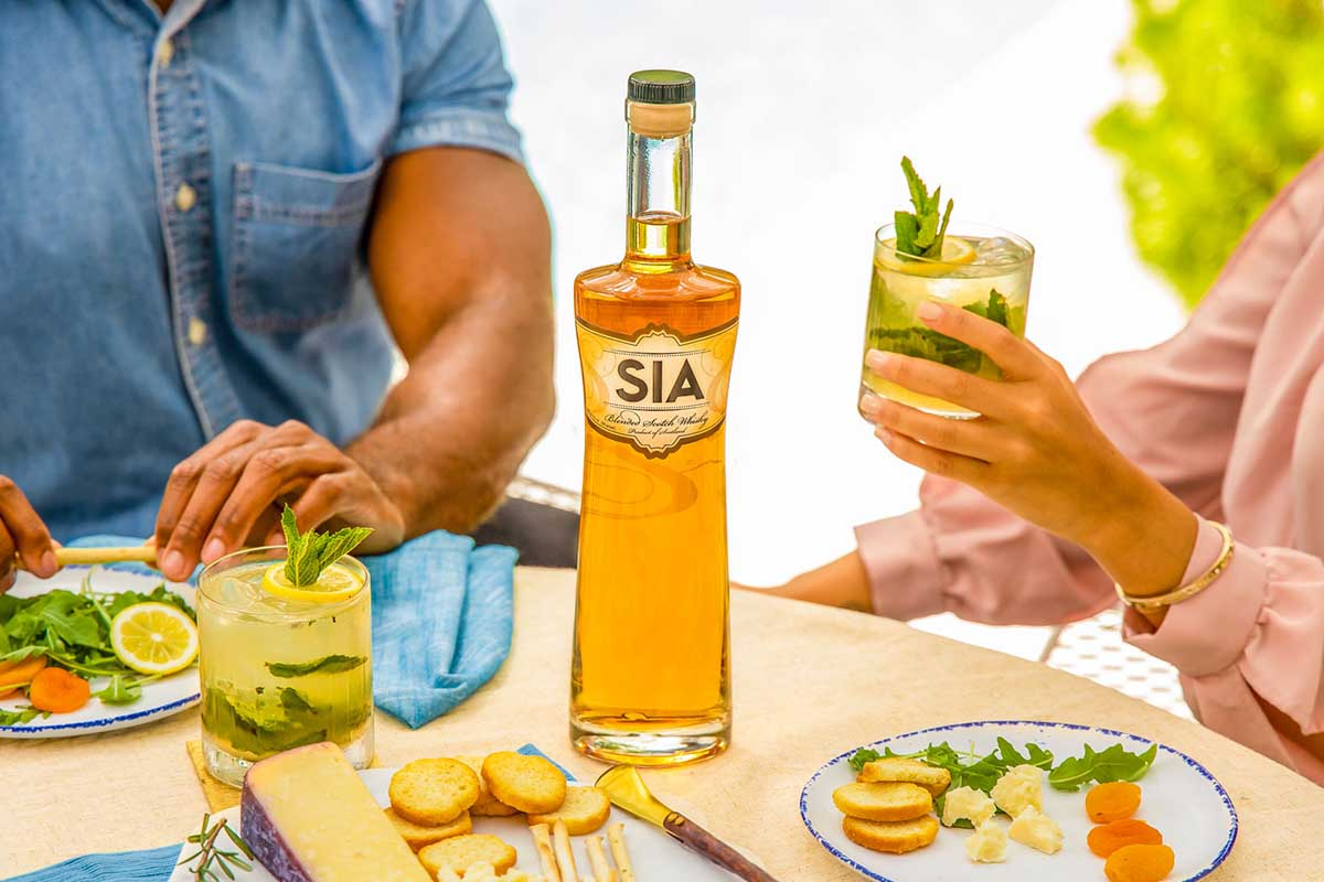 Two people at a dinner table sipping cocktails made from a bottle of SIA Scotch Whisky