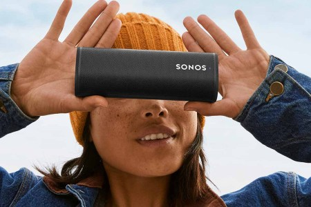 A woman outside holding a Sonos Roam speaker. Sonos teamed up with the North Face to provide outdoor adventure soundscapes on their streaming service.