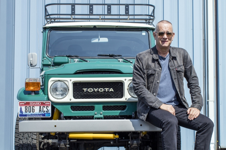 Actor Tom Hanks sitting on the bumper of his Toyota FJ40 Land Cruiser. The custom SUV, from TLC 4x4 and ICON 4x4, is headed to auction at Bonhams.