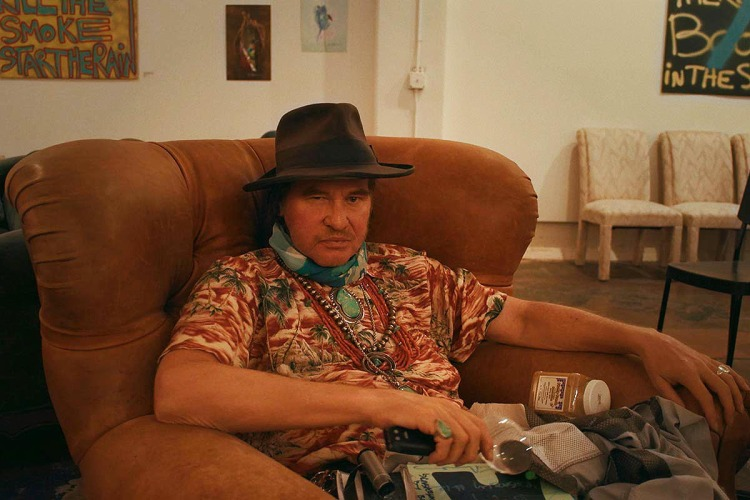 """Val Kilmer sitting down in the documentary """"Val"""", which was built from video the actor took over several decades"""