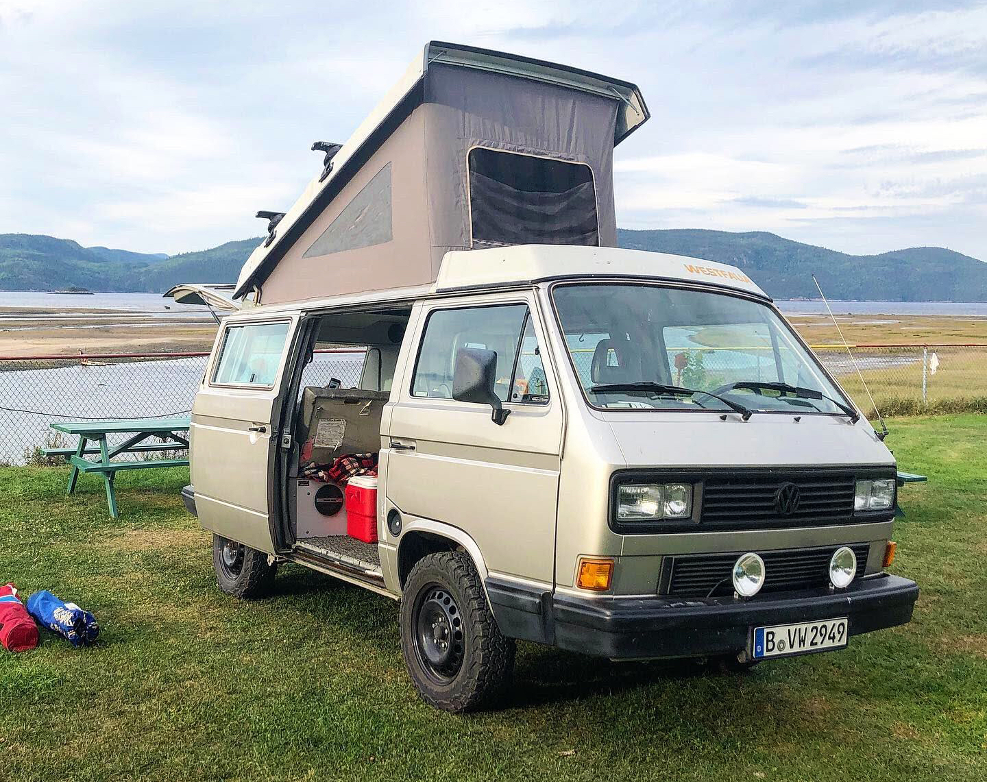 A photo of a 1990 Volkswagen Vanagon Westfalia with the pop-top tent extended. Here's a guide to buying your own camper van.