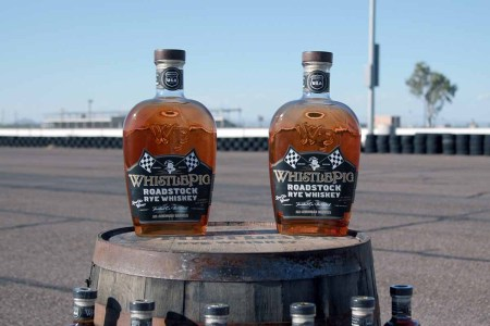 Two bottles of WhistlePig Roadstock Rye Whiskey sitting on a barrel on a track