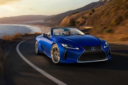 A man driving a blue 2021 Lexus LC 500 Convertible down a coastal road. The luxury grand tourer has become one of our favorites after test driving.