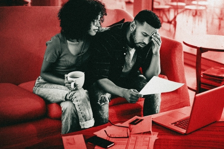 Financial infidelity occurs when a partner in a relationship lies or hides their financial circumstances from a partner. This photo shows a couple sitting on a couch together looking distressed while the man looks over financial documents.