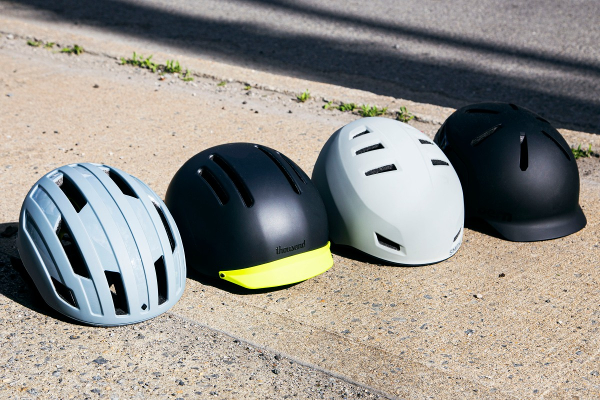 Four stylish, modern bicycle helmets — by Sweet Protection, Thousand, Smith and Bern, respectively — situated in a row on the sidewalk