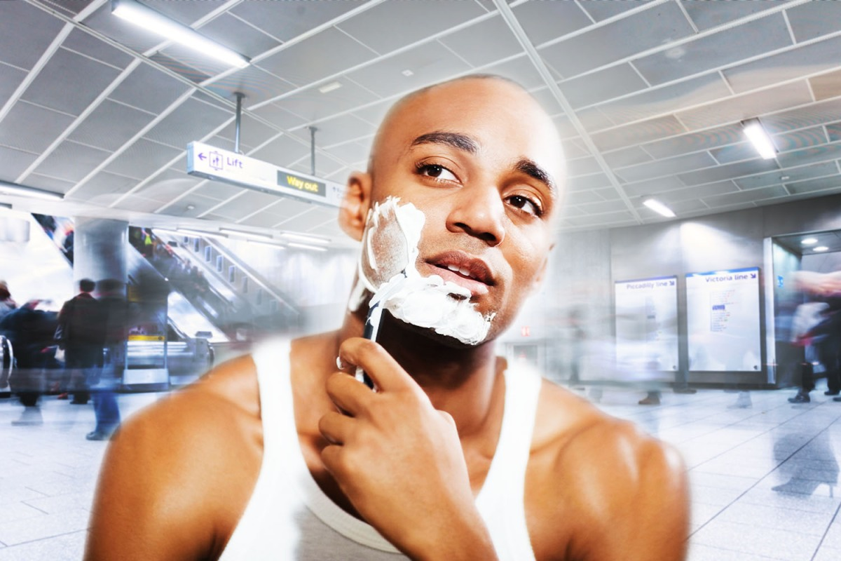 A young man in an undershirt shaving his face with a razor inside a busy airport terminal