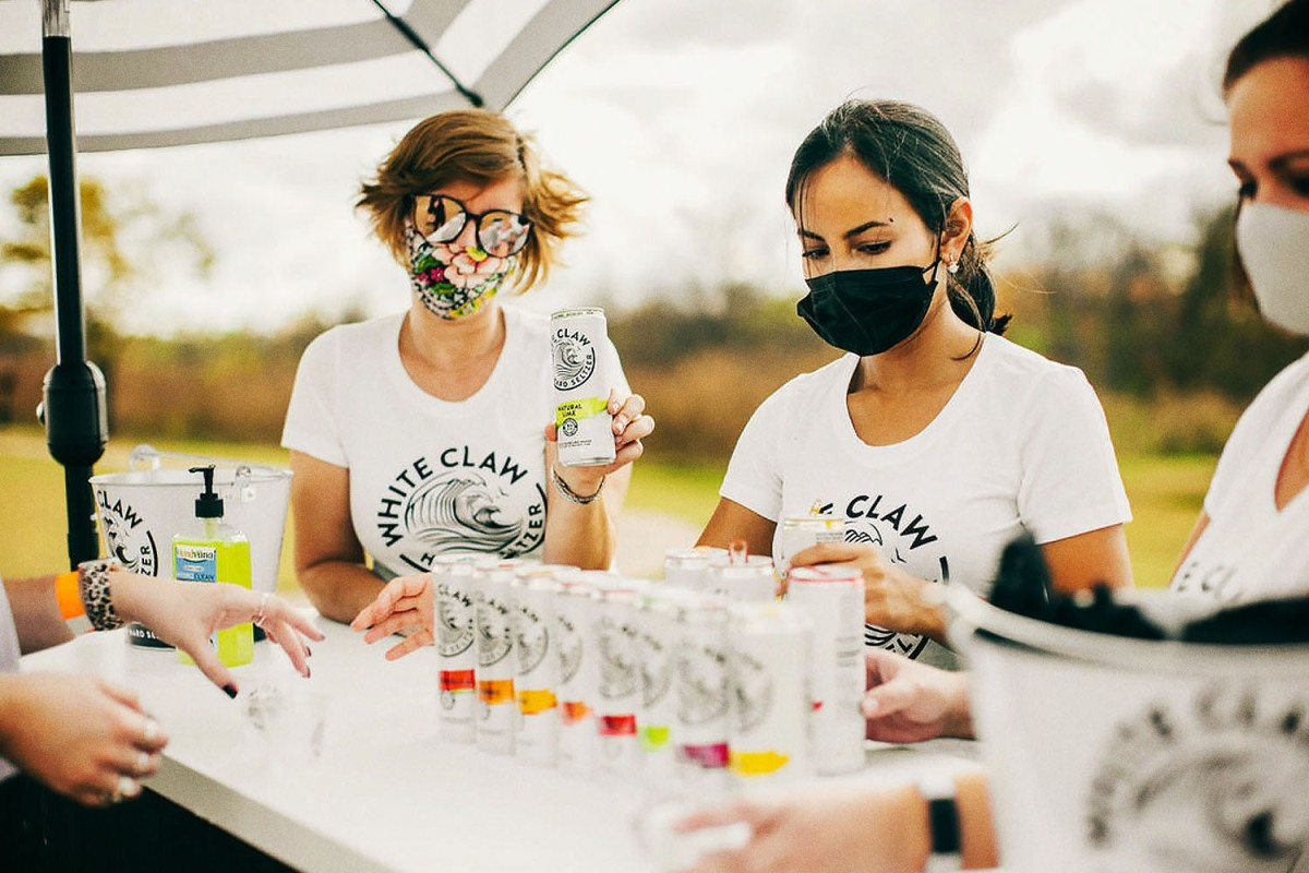Three people serving White Claw at Seltzerland, a new traveling festival devoted to hard seltzers