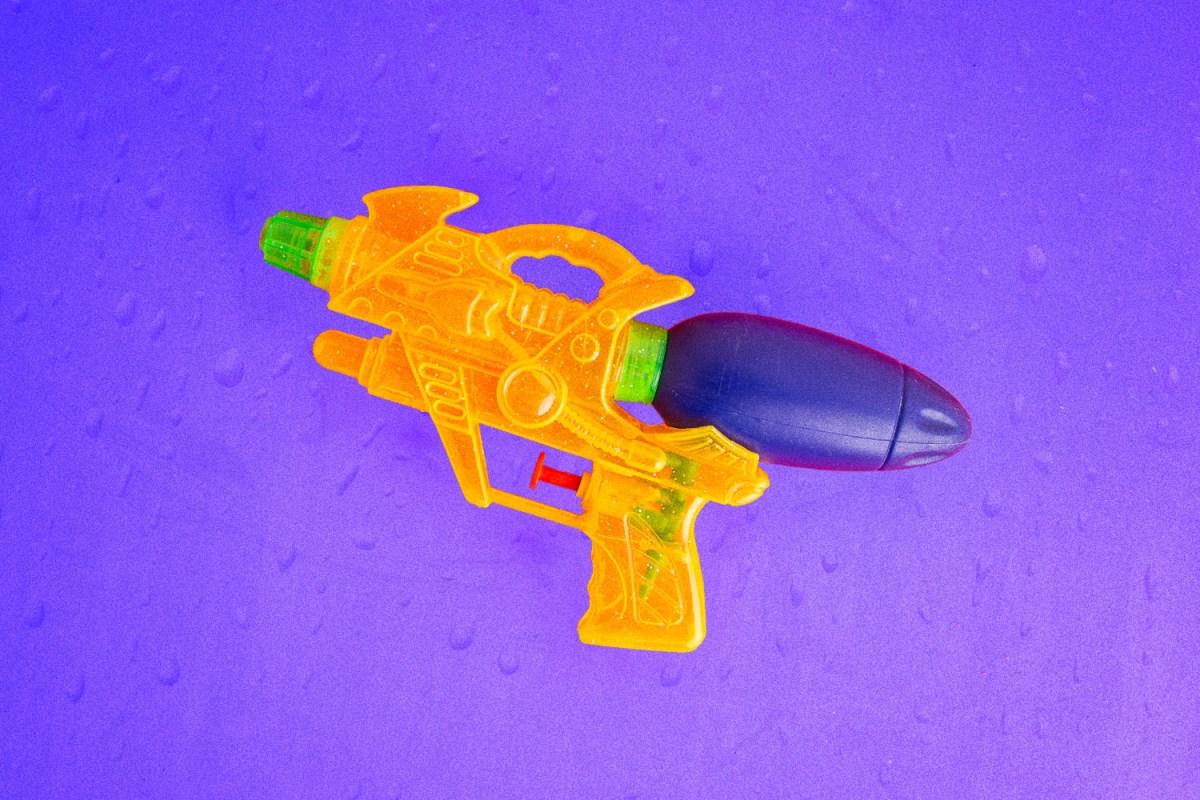 toy squirt gun on purple background