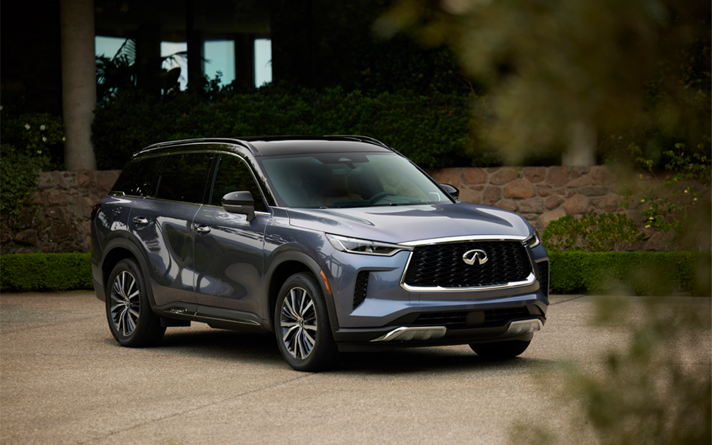 The all-new 2022 Infiniti QX60 luxury crossover sitting in a driveway next to a house with some greenery in the foreground