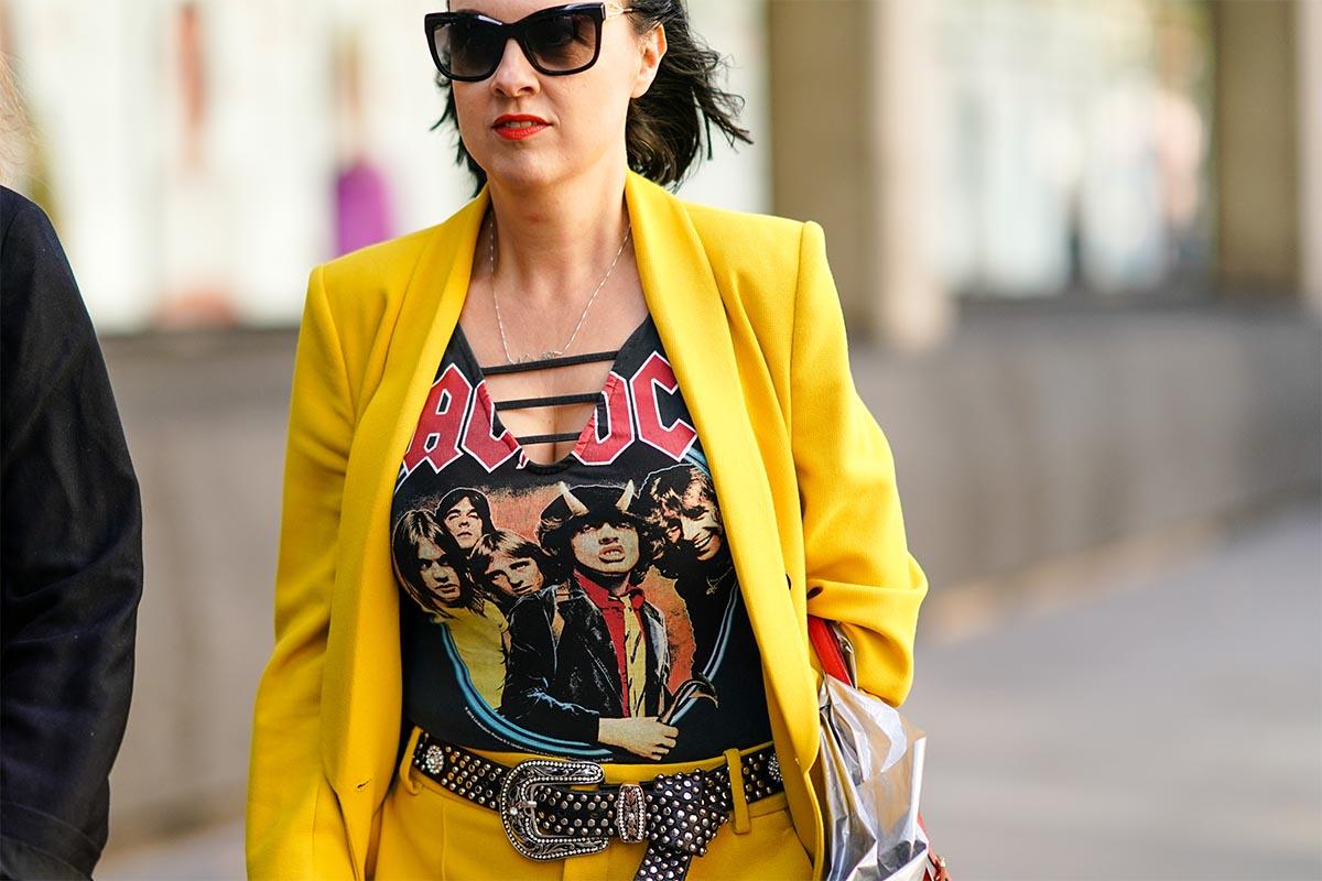 A guest wears sunglasses, an AC DC t-shirt, a studded belt, a yellow oversized blazer jacket, yellow pants, during London Fashion Week September 2019