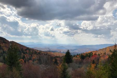 A view of a valley along the Appalachian Trail with white clouds in a blue sky and lots of trees with leaves changing colors