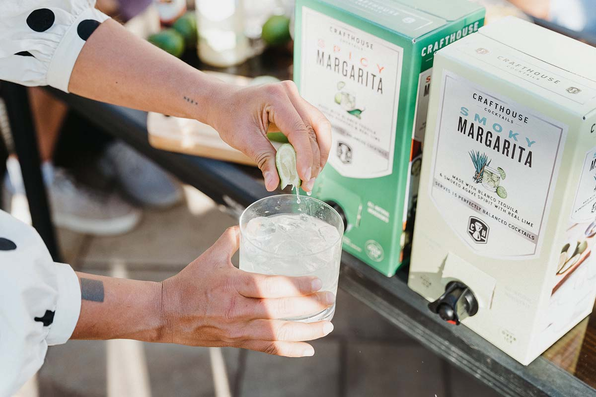 """A person (off-camera) squeezing a lime over a margarita from Crafthouse Cocktails. The brand is one of several that's launched a """"boxed cocktail"""" line, which makes it easier (and cheaper) to serve cocktails in a large-format setting"""