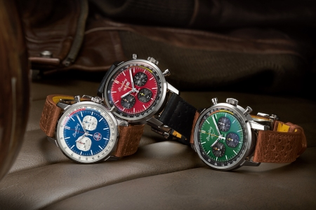 Three watches from Breitling's Top Time Classic Cars Capsule Collection sitting on the seat of a car with a leather jacket in the background