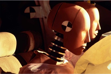 Crash-test dummies inside car with inflated airbags, close-up. Women are more likely to be hurt than men in car crashes due to poor design from government agencies who use crash test dummies.