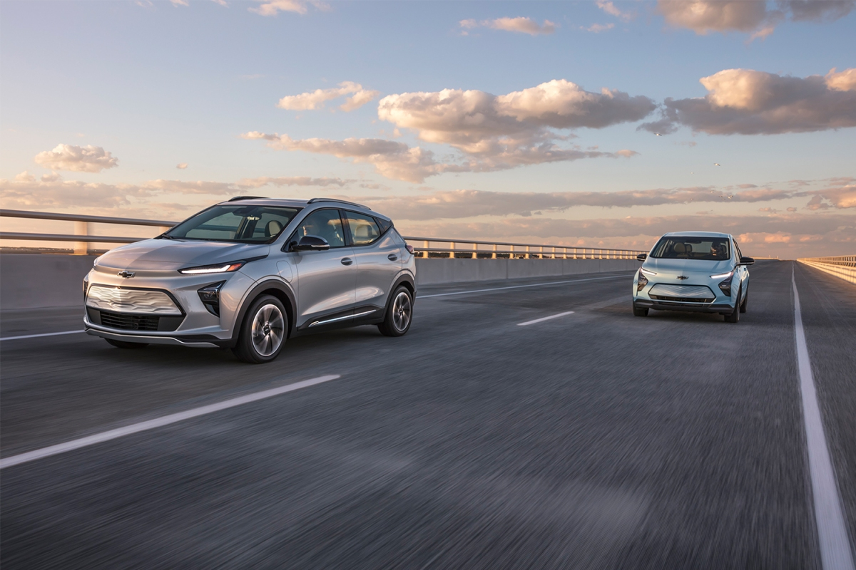 A Chevrolet Bolt EUV and Chevrolet Bolt EV driving down the highway. GM recalled all model years of the electric vehicles after risk of battery fires.